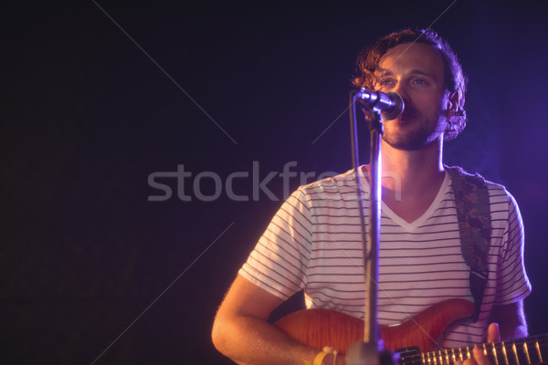 Confident male singer performing with guitar Stock photo © wavebreak_media