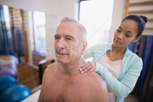 Stock photo: Shirtless senior male patient receiving neck massage from female therapist