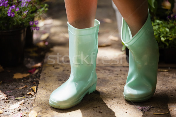 Low section of girl wearing green rubber boot standing on footpath Stock photo © wavebreak_media