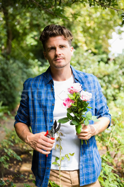Man trimming flowers with pruning shears in garden on a sunny day Stock photo © wavebreak_media