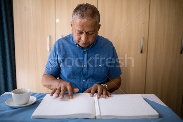 Senior man reading book at table Stock photo © wavebreak_media
