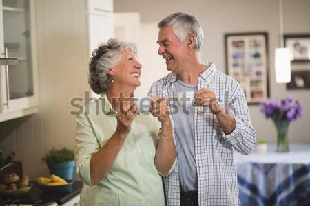 Sorridente casal de idosos copo de vinho cozinha casa Foto stock © wavebreak_media