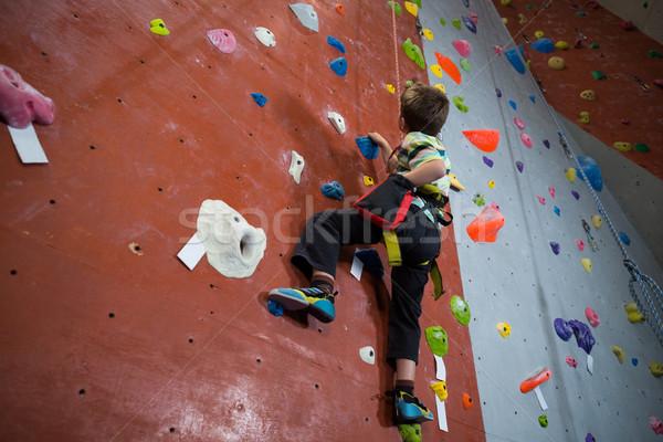 Boy practicing rock climbing in fitness studio Stock photo © wavebreak_media