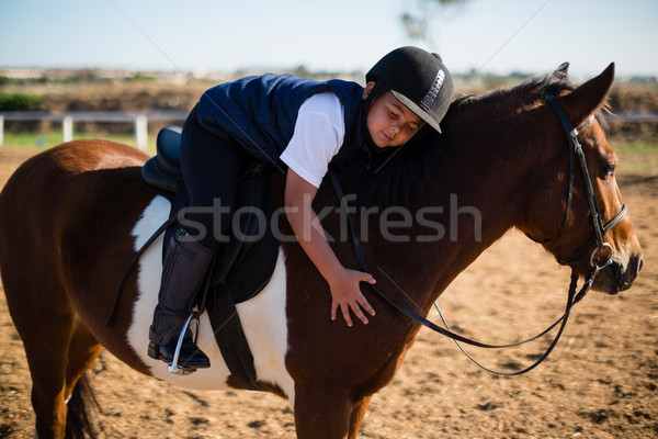 Smiling boy embracing the white horse in the ranch Stock photo © wavebreak_media