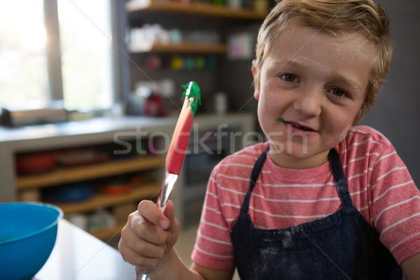 Portrait of boy holding spatula with batter Stock photo © wavebreak_media