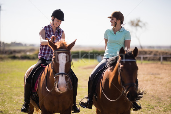 Full length happy female friends talking while horseback riding Stock photo © wavebreak_media