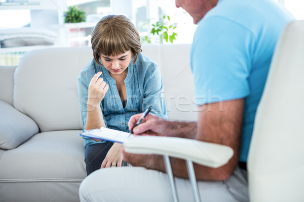 Doctor writing on notepad while consulting female patient Stock photo © wavebreak_media