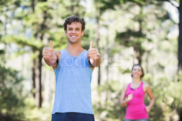 Man gesturing thumbs up with woman in background Stock photo © wavebreak_media