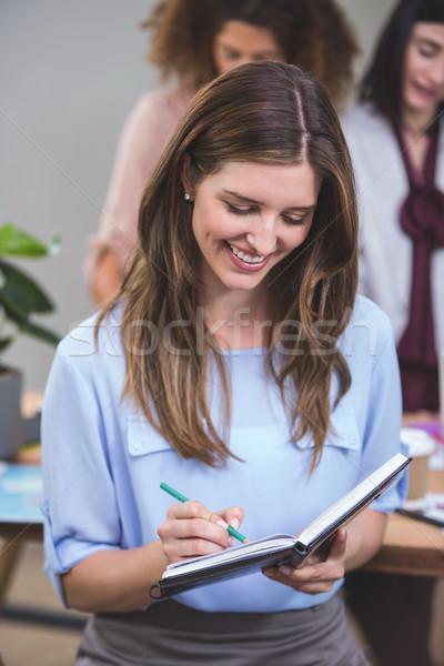 Empresária escrita nota diário escritório negócio Foto stock © wavebreak_media