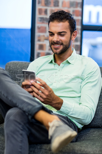 Young man text messaging on mobile phone Stock photo © wavebreak_media