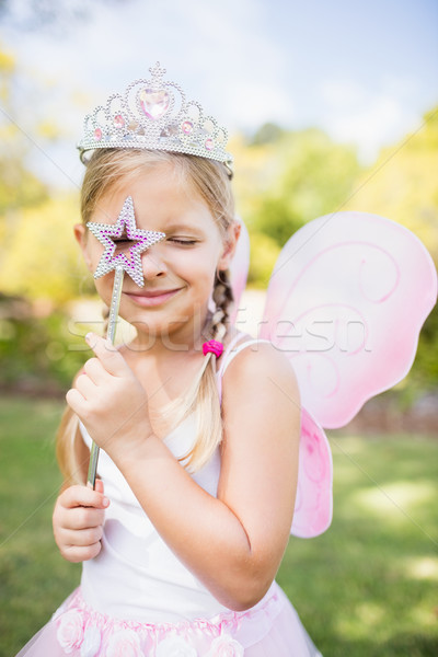 Portrait of cute girl with fairy dress looking across her magic  Stock photo © wavebreak_media