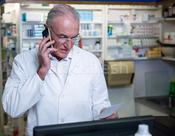 Farmacêutico falante telefone móvel prescrição farmácia negócio Foto stock © wavebreak_media