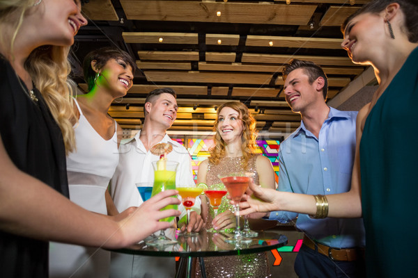 Group of friends interacting with each other while having cocktail Stock photo © wavebreak_media