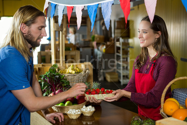 Smiling female staff offering strawberry to customer at organic section Stock photo © wavebreak_media