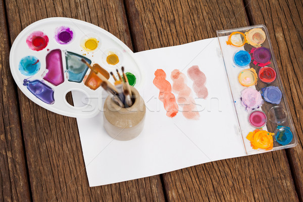 Paint brushes, watercolor paints, glass palette and white paper Stock photo © wavebreak_media