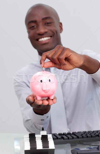 Happy Afro-American businessman saving money in a piggybank Stock photo © wavebreak_media