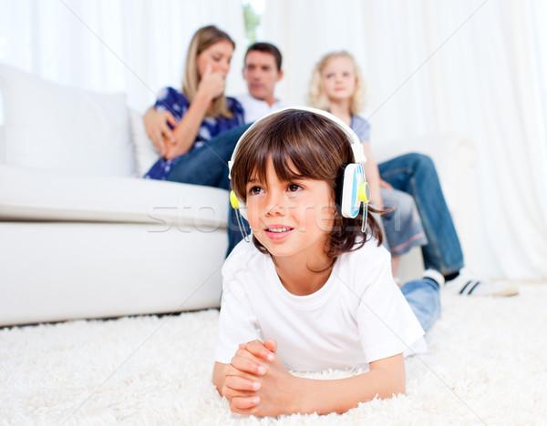 Smiling little boy listening music lying on floor Stock photo © wavebreak_media