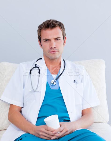 Grave doctor de sexo masculino potable café personal habitación Foto stock © wavebreak_media