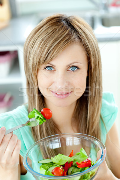 Radiant woman eating a salad in the kitchen  Stock photo © wavebreak_media