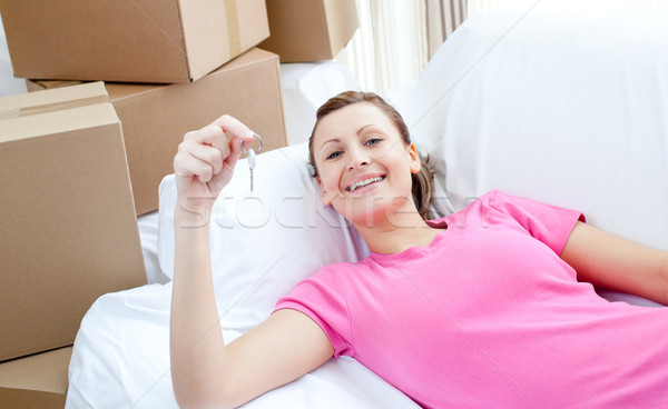 Self-assured woman relaxing on a sofa with boxes Stock photo © wavebreak_media
