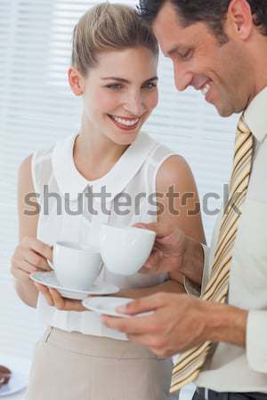 Enamored couple drinking a cup of tea lying on their bed Stock photo © wavebreak_media