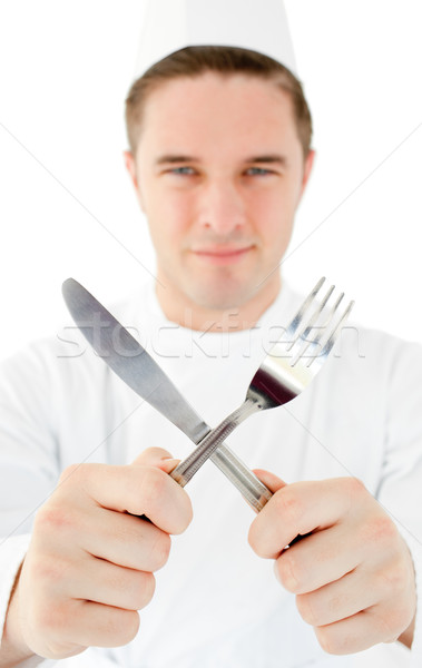 Handsome cook holding cutlery against white background  Stock photo © wavebreak_media