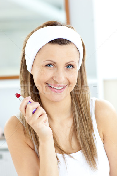 Joyful young woman holding a red lipstick smiling at the camera in the bathroom Stock photo © wavebreak_media