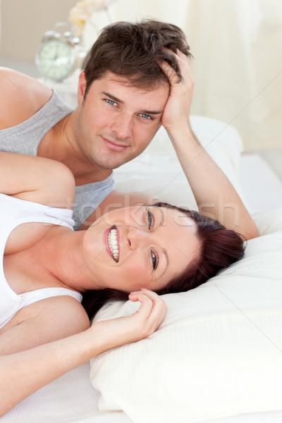 Radiant caucasian couple lying on bed in their bedroom Stock photo © wavebreak_media