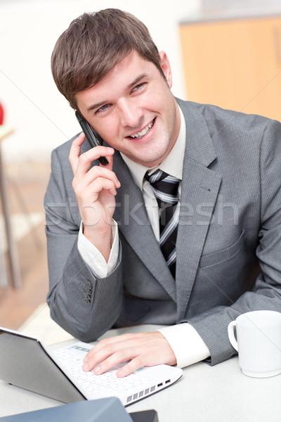 Charyzmatyczny biznesmen za pomocą laptopa mówić telefonu pracy Zdjęcia stock © wavebreak_media