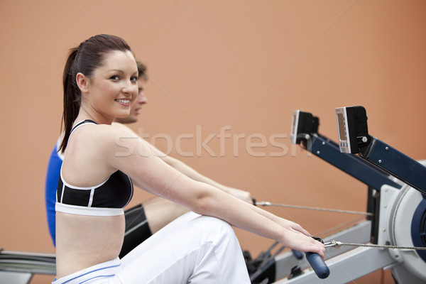 Happy woman with her boyfriend using a rower in a fitness centre Stock photo © wavebreak_media