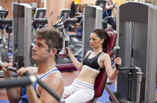 Concentrated couple using shoulder press in a fitness centre Stock photo © wavebreak_media