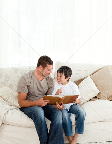 Stock photo: Adorable boy looking at a photo album with his father on the sofa at home