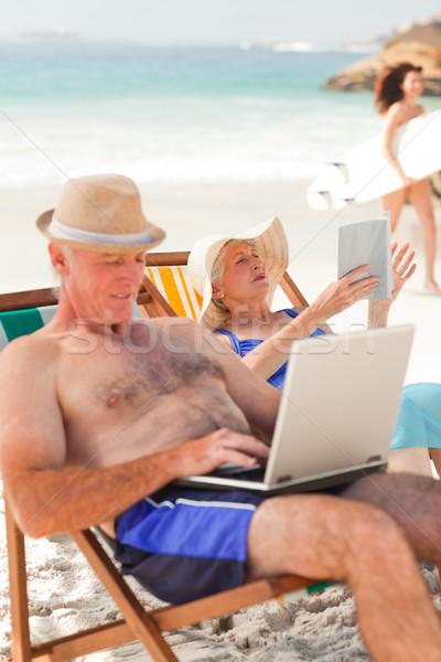 Férfi dolgozik laptop feleség olvas tengerpart Stock fotó © wavebreak_media