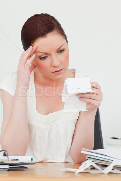 Young attractive red-haired female being depressed by the amount of the receipt while sitting at a d Stock photo © wavebreak_media