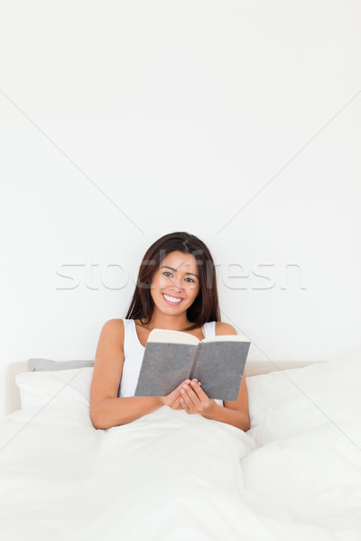 dark-haired woman holding book sitting in bed looking into camera in bedroom Stock photo © wavebreak_media