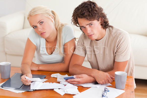 Unhappy couple looking into the camera in the living room Stock photo © wavebreak_media