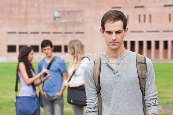 Stock photo: Lonely student posing while his classmates are talking outside a building