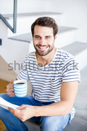 Smiling young student leaning on a stack of books Stock photo © wavebreak_media
