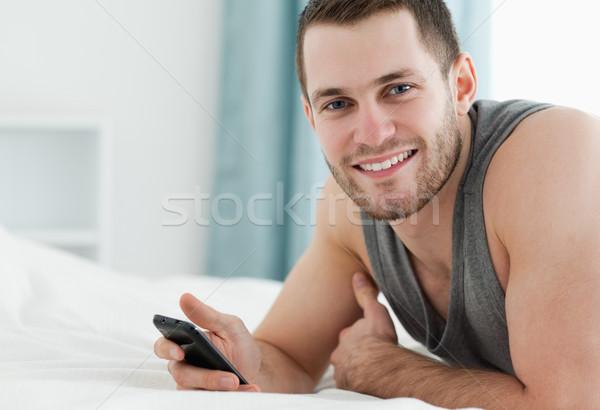 Uśmiechnięty człowiek telefonu komórkowego sypialni uśmiech telefonu Zdjęcia stock © wavebreak_media