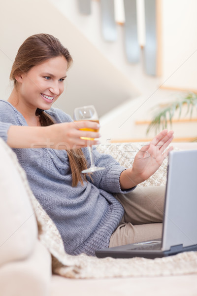 Stock photo: Portrait of a woman having a glass of white wine during a video conference in her living room