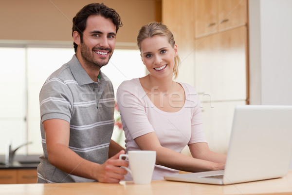 Smiling couple using a notebook while having coffee in their kitchen Stock photo © wavebreak_media