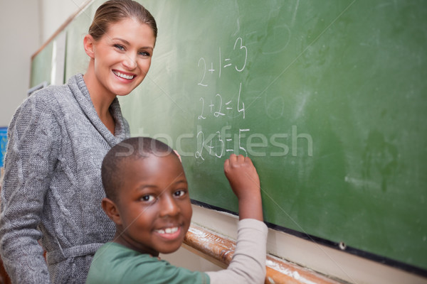 Smiling teacher and a pupil making an addition on a blackboard Stock photo © wavebreak_media