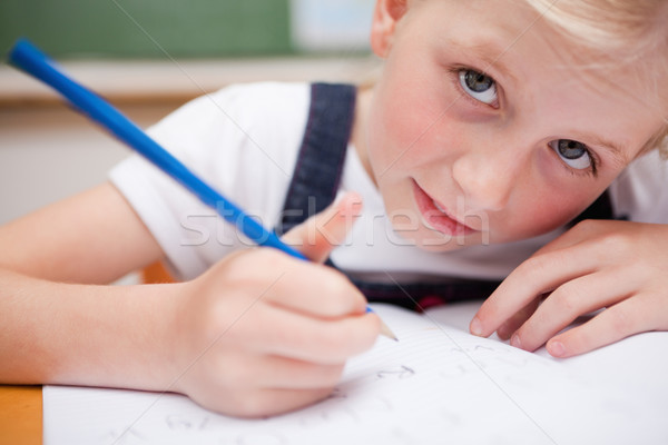 Close up of a serious schoolgirl writing something in a classroom Stock photo © wavebreak_media