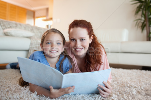 Mother and daughter looking at periodical together Stock photo © wavebreak_media