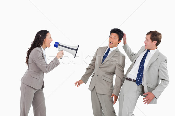 Businesswoman with megaphone yelling at colleagues against a white background Stock photo © wavebreak_media