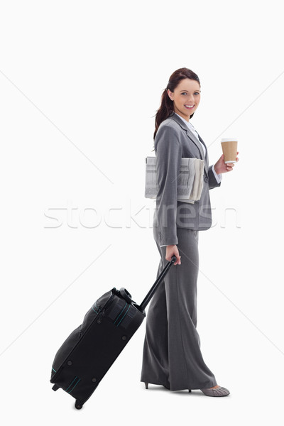 Profile of a businesswoman smiling with a suitcase, a newspaper and a coffee against white backgroun Stock photo © wavebreak_media