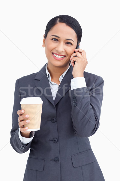 Close up of smiling saleswoman with paper cup and cellphone against a white background Stock photo © wavebreak_media