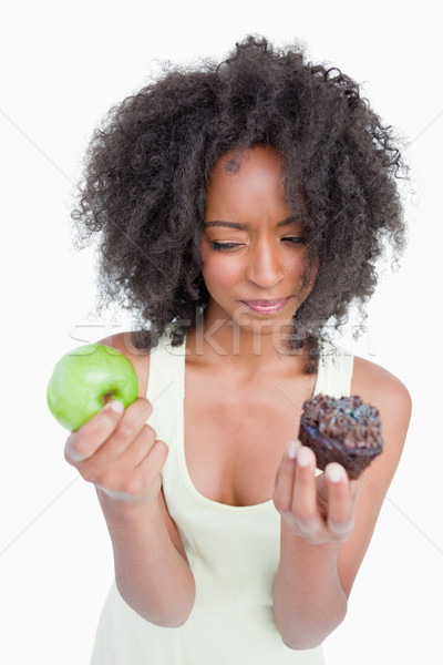 Young woman hesitating between a muffin and an apple against a white background Stock photo © wavebreak_media