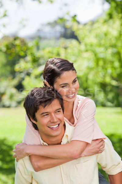 Frau lächelnd schauen Seite Freund tragen zurück Stock foto © wavebreak_media