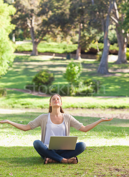 Woman sitting on the lawn in a yoga position with a laptop Stock photo © wavebreak_media